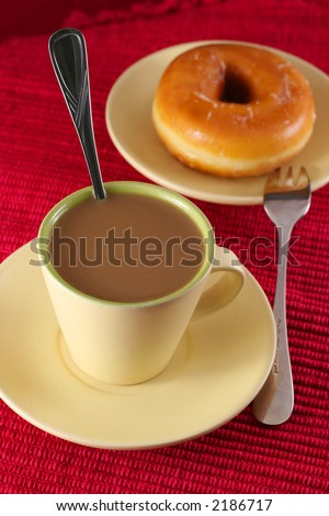 coffee and donut with fork and spoon on red table cloth - stock photo
