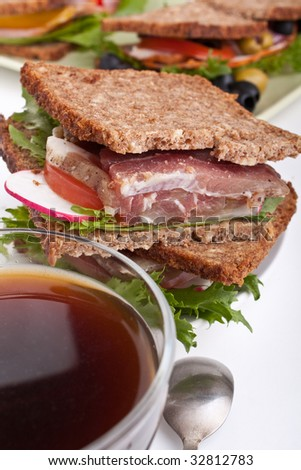 coffee and group of big healthy sandwiches made with whole grain bread, lettuce, vegetables and meat