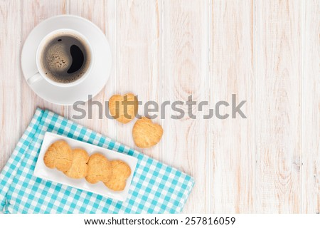 Coffee and heart shaped cookies on white wooden table with copy space - stock photo