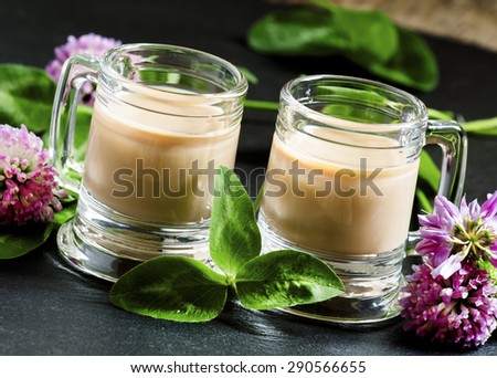 Coffee and Irish cream liqueur with flowers and clover shamrock in vintage mugs, selective focus - stock photo
