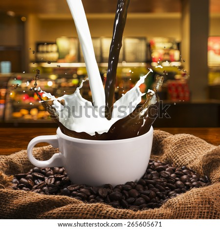 Coffee and Milk Splash from Cup. Coffee Shop in Background - stock photo