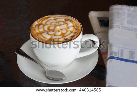 Coffee and newspaper on a table in a coffee shop. - stock photo
