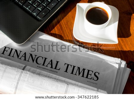 Coffee and notebook and newspaper with inscription financial time - stock photo