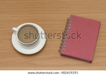coffee and notebook on wooden table