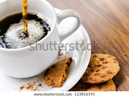 Coffee and oatmeal cookies on wooden table. - stock photo