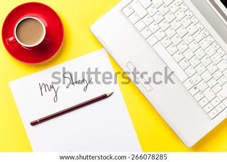 coffee and paper with My Story words near notebook on yellow background - stock photo
