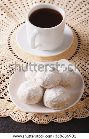 Coffee and polvoron cookies with powdered sugar close-up on a plate. vertical