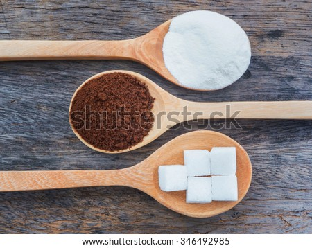 Coffee and powdered milk with sugar cubes on wooden spoon - stock photo