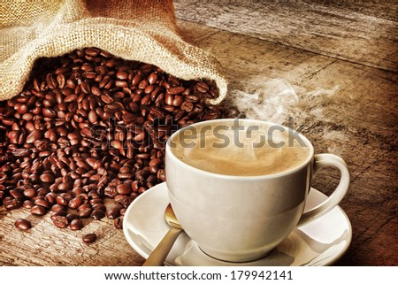 Coffee and Sack of Coffee Beans - a cup of hot steaming espresso coffee on a rustic plank background, with a sack of coffee beans. Front to back focus. Instagram effect. - stock photo