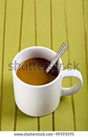 Coffee and Spoon in White Mug on Green Placemat - stock photo