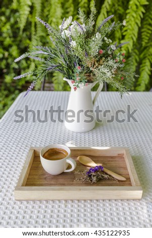 Coffee and spring flowers on wooden tray, Espresso coffee in wooden tray place on Table in garden, Espresso coffee with wooden tray and wooden spoon on white table in garden - stock photo