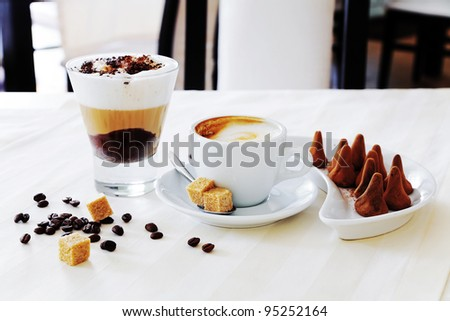 coffee and sweat candies on white table - stock photo