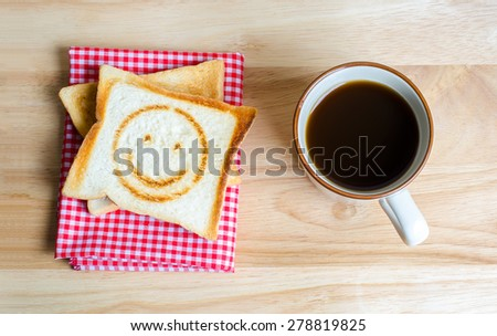 Coffee and toasts on wooden table - stock photo
