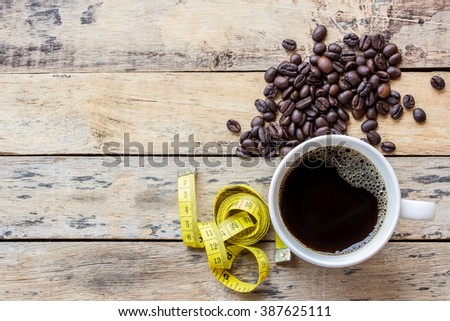 Coffee and yellow measuring tape on wooden table background - stock photo