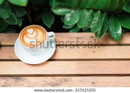 Coffee art on Wood table with green tree leaves - stock photo
