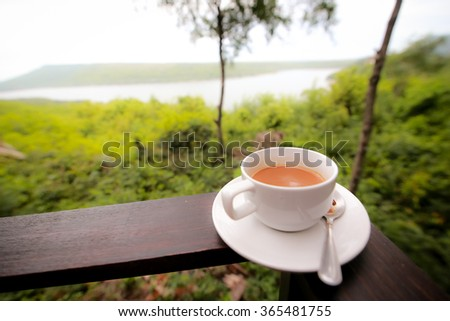 Coffee at the Beach/ A cup of coffee in front of a blue sea.  - stock photo