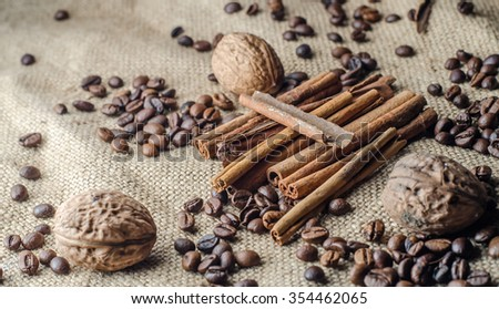 Coffee background coffee beans, cinnamon sticks, walnuts, brown fabric background,horizontal photo