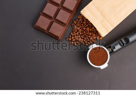 Coffee background - top view. Coffee in a holder, coffee beans, bar of chocolate - stock photo