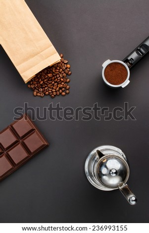 Coffee background - top view. Coffee in a holder, coffee beans, bar of chocolate, coffee-pot - stock photo