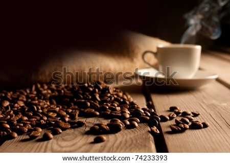 Coffee background with beans and white cup. Dark atmosphere and copy space. - stock photo