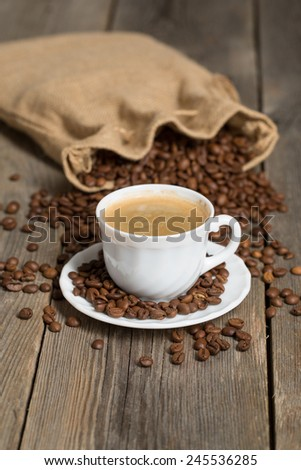 Coffee bag full of coffee beans and white cup of coffee in front. Placed on an old wooden background.