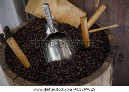 coffee bean and spoon in wood barrel tank,Cup of coffee, bag and scoop on old rusty background
