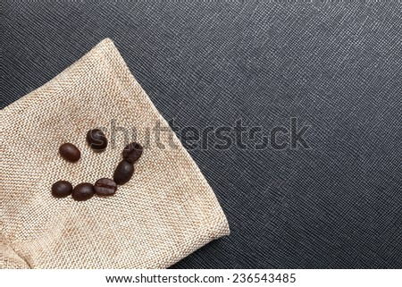 Coffee bean arrange to the shape of smiling face put on the coffee bean sack in the scene appear the back color leather background. - stock photo