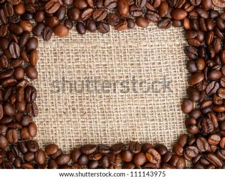 Coffee bean frame on jute background. - stock photo