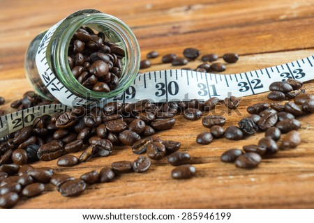Coffee bean in glass bottle with tape measure on wooden table background - stock photo