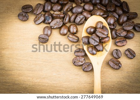 coffee bean in wooden spoon on wood table,soft focus. - stock photo