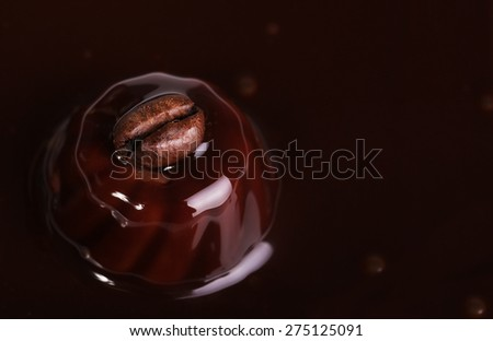 Coffee bean on malted chocolate. Liquid chocolate - stock photo
