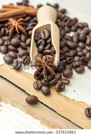 Coffee beans and an old wooden scoop - stock photo