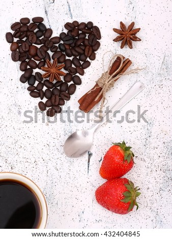 Coffee beans and anise with strawberry arranged in a heart on a white wooden background. - stock photo