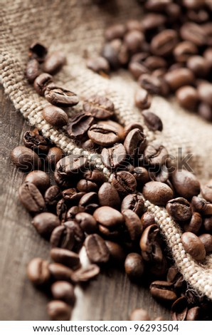 Coffee beans and burlap fabric - stock photo