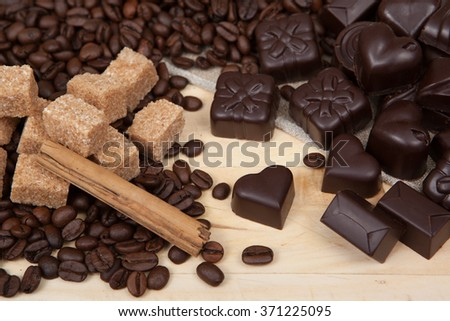 Coffee beans and chocolate candies on a linen cloth and wooden plank. - stock photo
