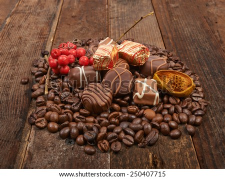 Coffee beans and chocolate pralines on a wooden background - stock photo