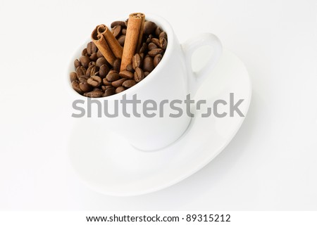Coffee beans and cinnamon in white cup over white background. Shallow DOF. - stock photo