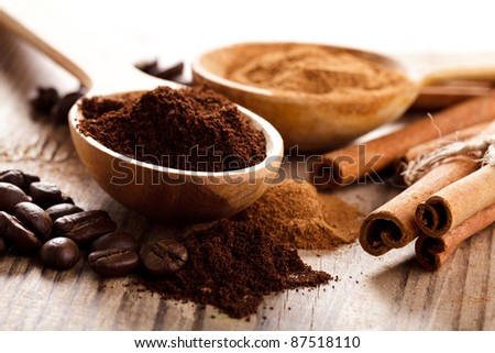 Coffee beans and cinnamon milled closeup in wooden spoons - stock photo