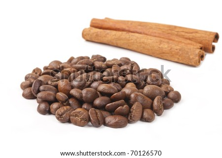 Coffee beans and cinnamon sticks on a white background. A shot horizontal. - stock photo