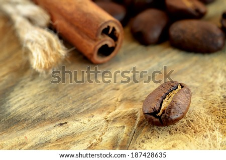 Coffee beans and cinnamon sticks on wooden background - stock photo