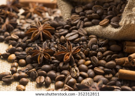 coffee beans and cinnamon with star anise scattered out of the bag
