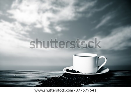 Coffee beans and coffee in white cup on wooden table opposite a defocused blue sky for background. Collage. Selective focus. Toned. - stock photo