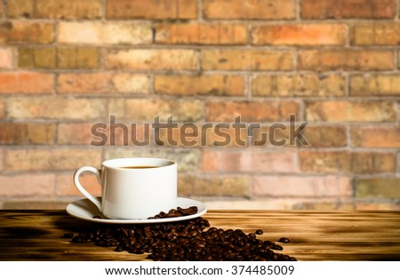 Coffee beans and coffee in white cup on wooden table opposite a defocused brick wall for background. Collage. Selective Focus. - stock photo