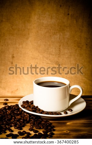 Coffee beans and coffee in white cup on wooden table opposite a defocused burlap background. Toned. - stock photo