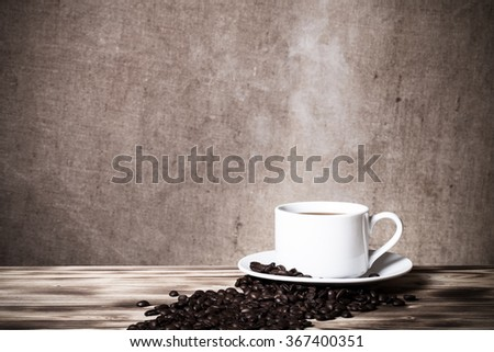 Coffee beans and coffee in white cup on wooden table opposite a defocused burlap background. Toned.