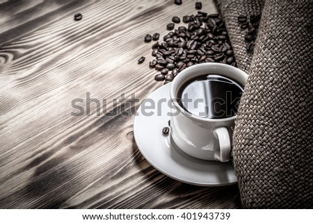 Coffee beans and coffee in white cup on wooden table with burlap. Selective focus. Toned. - stock photo