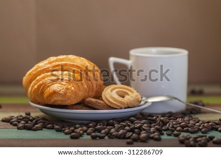Coffee beans and cookies with croissant - stock photo