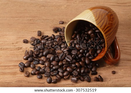 coffee beans and cup on wood