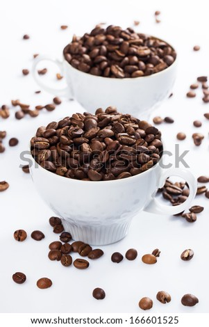 Coffee beans and cups over white background - stock photo