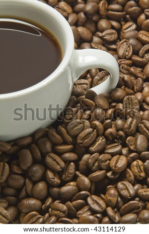 Coffee Beans and cut of black coffee, with copy space.
